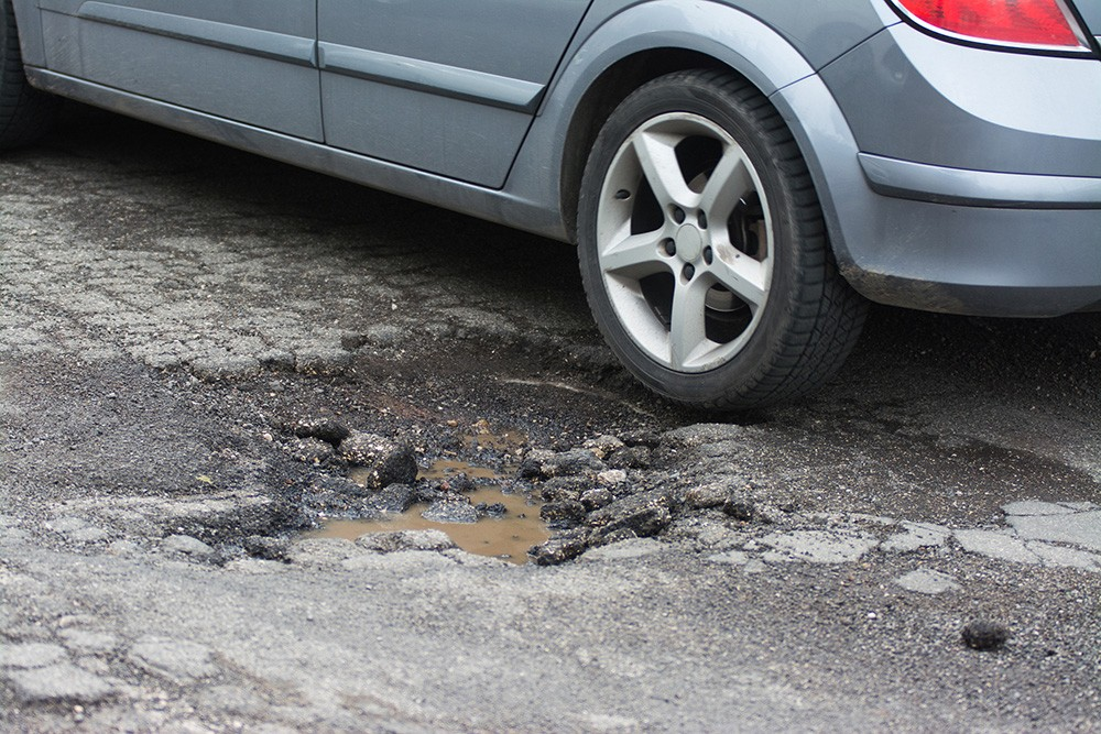 Car driving over pothole